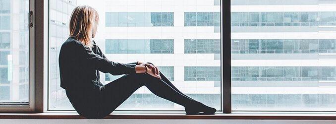 Frau sitzt auf Fensterbank und schaut raus auf ein Gebäude